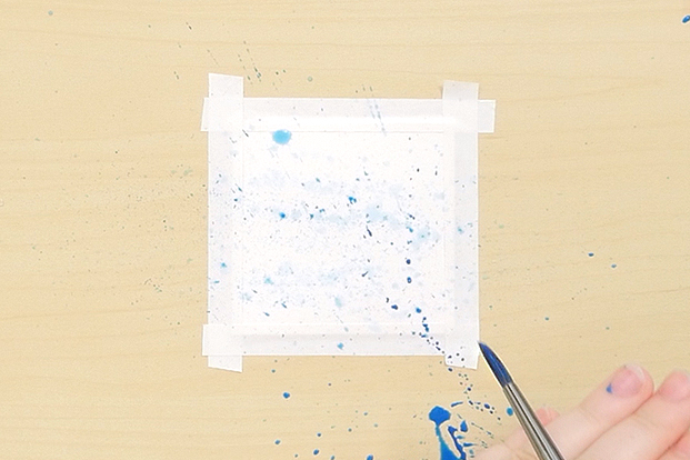 Flick paint onto your paper.
