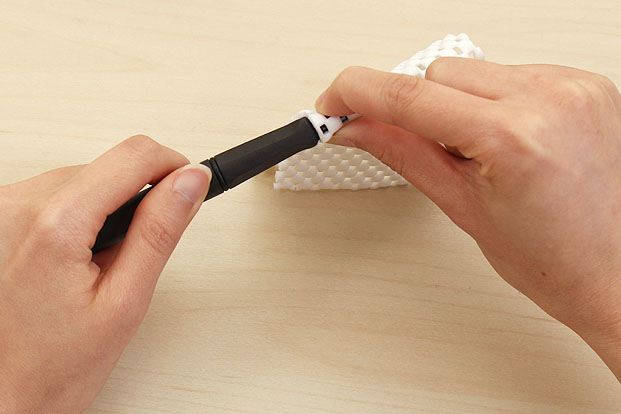Place your index finger and thumb around the sides of the nib.